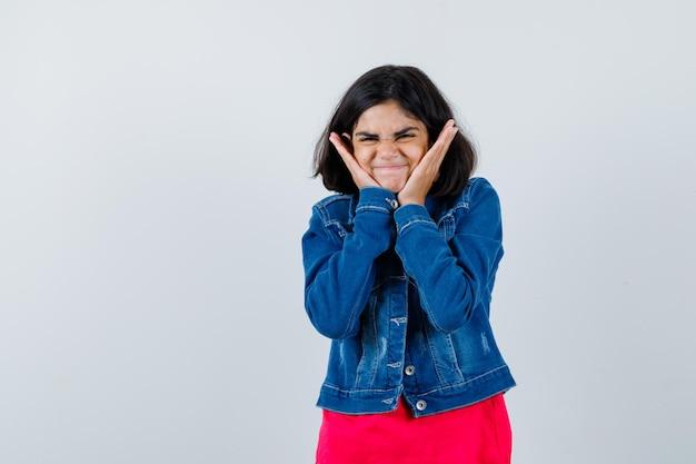 Jong meisje handen op wangen in rood t-shirt en spijkerjasje zetten en op zoek gelukkig, vooraanzicht.