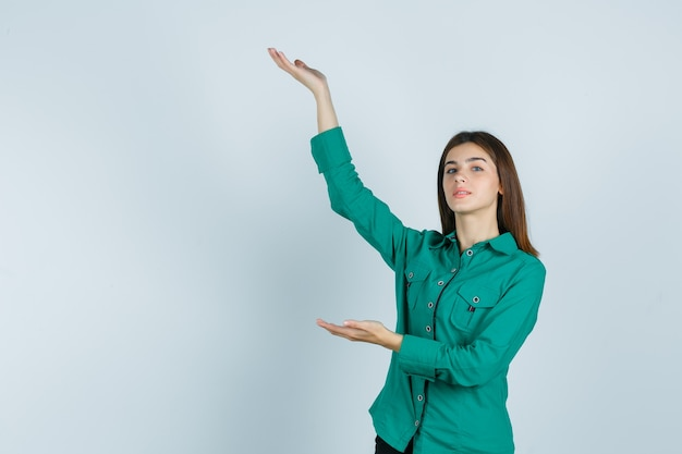 Jong meisje handen uitrekken als iets in groene blouse, zwarte broek vast te houden en op zoek naar ernstige, vooraanzicht.