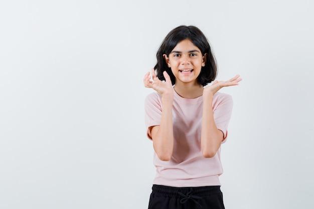 Jong meisje handen uitrekken als iets in roze t-shirt en zwarte broek presenteren en gelukkig kijken