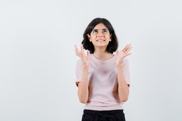 Jong meisje handen uitrekken als iets in roze t-shirt en zwarte broek vasthouden en gelukkig kijken