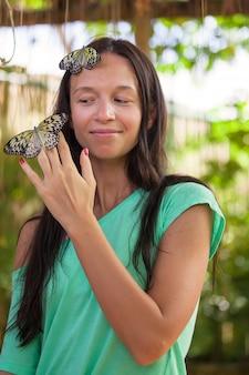 Jong meisje het letten op vlinders in een natuurlijke tuin