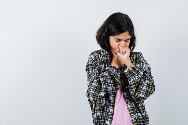 Jong meisje hoest in geruit overhemd en roze t-shirt en ziet er uitgeput uit. vooraanzicht.