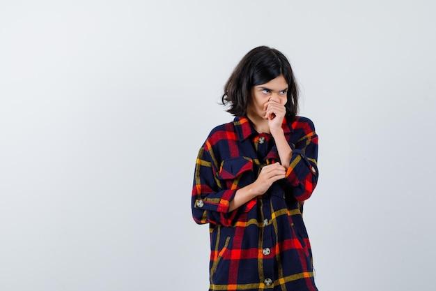 Jong meisje hoest in geruit overhemd en ziet er ziek uit, vooraanzicht.