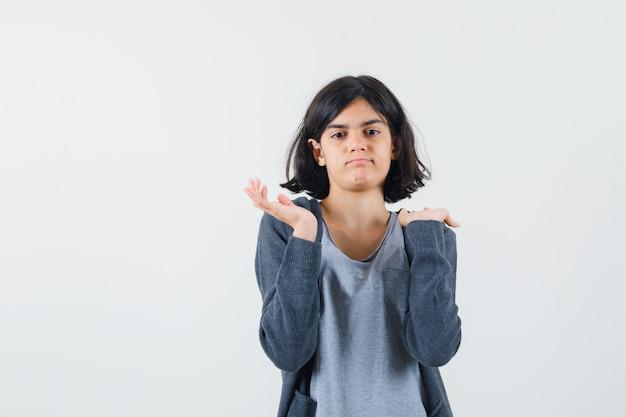 Jong meisje houdt een hand op de schouder, een andere hand strekt zich uit in een lichtgrijs t-shirt en een donkergrijze hoodie met ritssluiting en ziet er schattig uit.