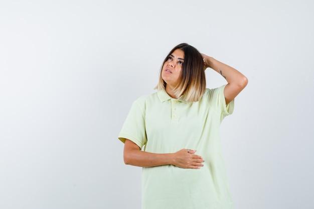 Jong meisje houdt een hand op het hoofd, een andere hand op de buik, denkt aan iets in een t-shirt en kijkt peinzend, vooraanzicht.