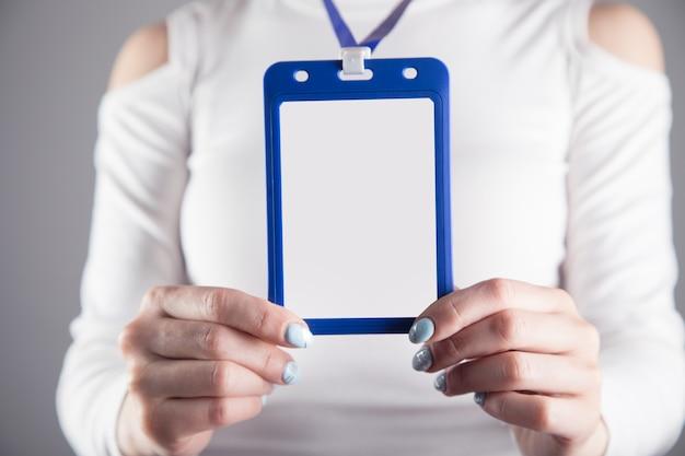 Jong meisje houdt een identiteitskaart op een grijze scène