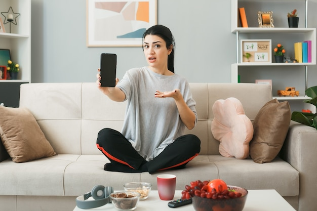 Jong meisje houdt en wijst met de hand naar de telefoon zittend op de bank achter de salontafel in de woonkamer