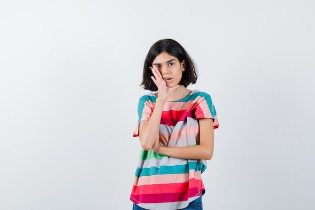 Jong meisje houdt hand in de buurt van mond als geheim in kleurrijk gestreept t-shirt en kijkt verrast. vooraanzicht.