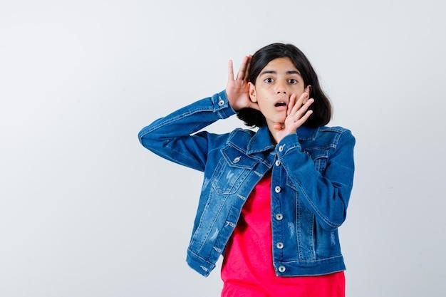 Jong meisje houdt hand in de buurt van mond en oor in rood t-shirt en spijkerjasje en ziet er schattig uit