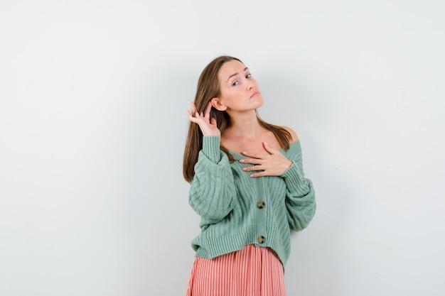 Jong meisje houdt hand in de buurt van oog, houdt hand over schouder in gebreide kleding, rok en kijkt gefocust, vooraanzicht.