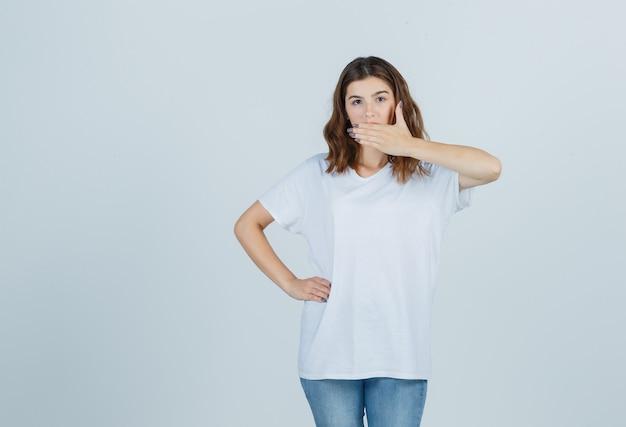 Jong meisje houdt hand op mond in wit t-shirt en kijkt verbaasd, vooraanzicht.