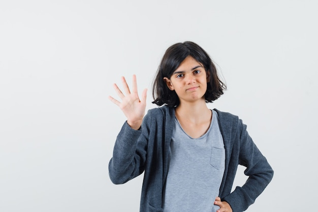 Jong meisje houdt hand op taille, hand opsteken als begroeting van iemand in lichtgrijs t-shirt en donkergrijze hoodie met ritssluiting en ziet er schattig uit.