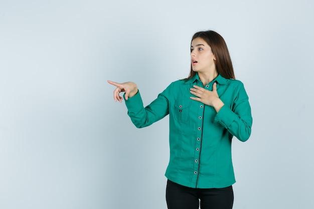 Jong meisje houdt hand over borst, wijst naar links met wijsvinger in groene blouse, zwarte broek en kijkt verbaasd, vooraanzicht.