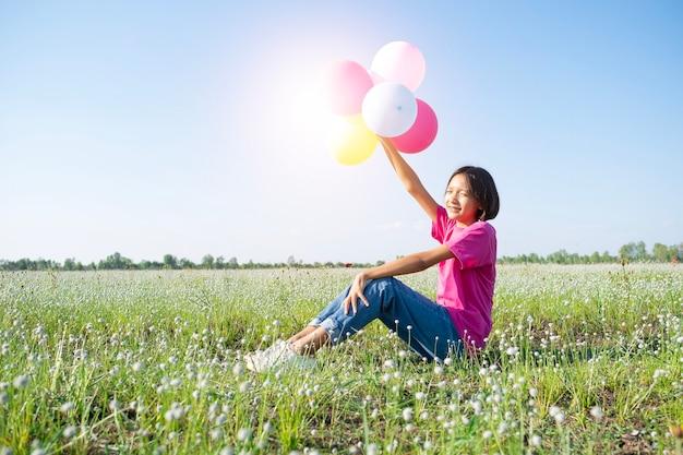 Jong meisje houdt kleurrijke ballonnen vast bij bloemgras met blauwe lucht