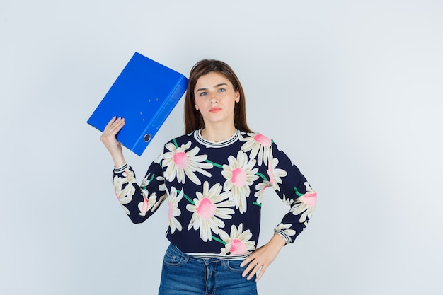 Jong meisje houdt map in de buurt van hoofd in bloemen blouse, jeans en kijkt verbaasd, vooraanzicht.