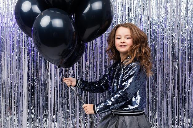 Jong meisje houdt met luchtige zwarte helium ballonnen op een schitterende feestelijke muur