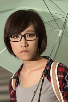 Jong meisje houdt paraplu en staat op straat in taipei, taiwan.