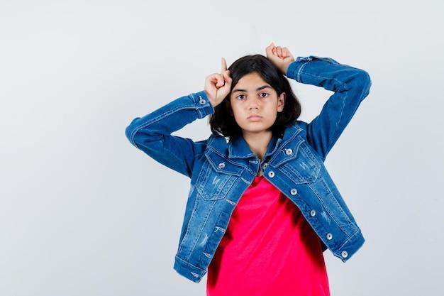 Jong meisje houdt vingers boven het hoofd als stierenhoorns in rood t-shirt en spijkerjasje en ziet er schattig uit.