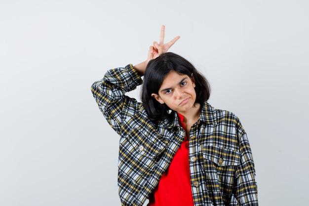 Jong meisje houdt vingers boven het hoofd als vredesgebaar in geruit overhemd en rood t-shirt en ziet er serieus uit, vooraanzicht.