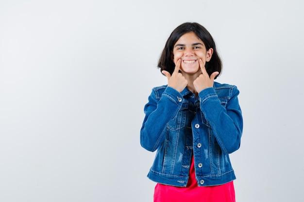 Jong meisje houdt wijsvingers in de buurt van mond, dwingt een glimlach in rood t-shirt en spijkerjasje en ziet er gelukkig uit, vooraanzicht.
