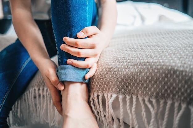 Jong meisje houdt zich vast aan een pijnlijk been. detailopname