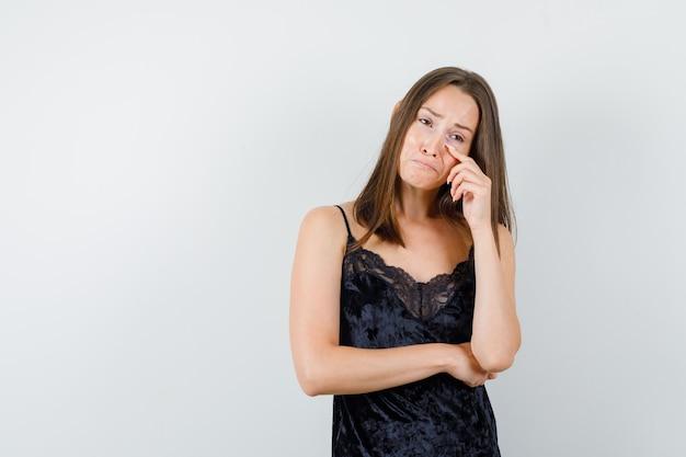 Jong meisje huilt terwijl ze wegkijkt in zwarte hemd en er bedroefd uitziet