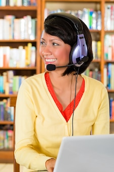 Jong meisje in bibliotheek met laptop en hoofdtelefoons