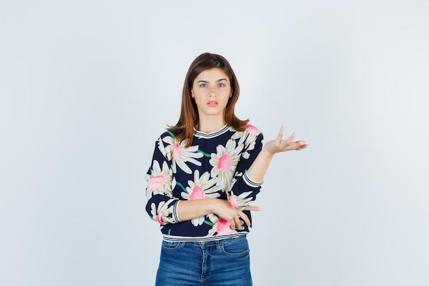 Jong meisje in bloementrui, jeans die zich op een vragende manier uitstrekt en perplex kijkt, vooraanzicht.