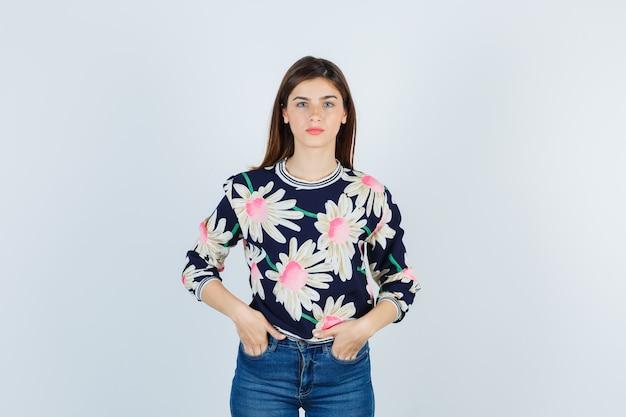 Jong meisje in bloementrui, jeans met handen in de zak en er serieus uitziend, vooraanzicht.