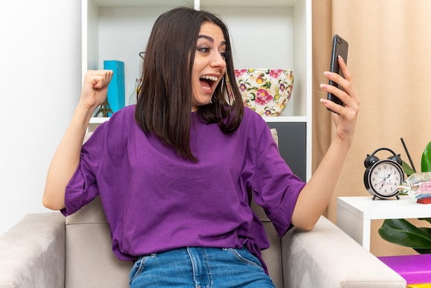 Jong meisje in casual kleding met smartphone balde vuist blij en opgewonden schreeuwen vreugde haar succes zittend op een stoel in lichte woonkamer