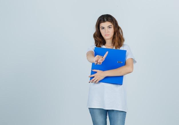 Jong meisje in de witte map van de t-shirtholding, die wacht op een minuutgebaar toont en zelfverzekerd kijkt, vooraanzicht.