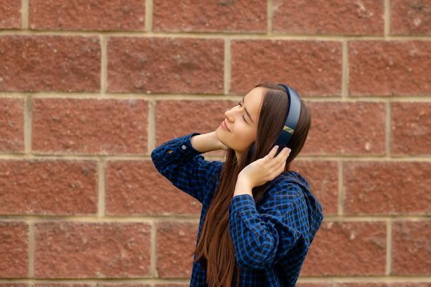 Jong meisje in draadloze koptelefoon luisteren naar muziek via mobiele telefoon