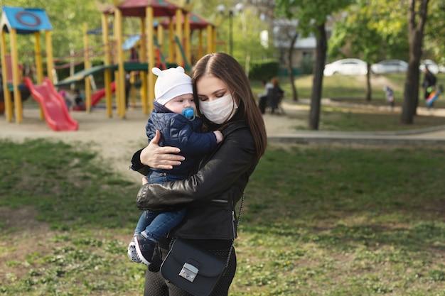 Jong meisje in een beschermend masker, knuffels haar kleine kind. covid-19