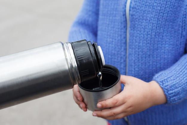 Jong meisje in een blauwe gebreide trui drinkt thee of koffie uit een thermoskan cup buitenshuis.