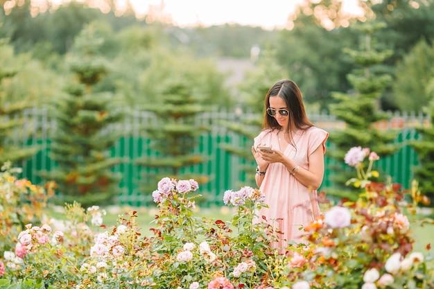 Jong meisje in een bloementuin onder mooie rozen. geur van rozen
