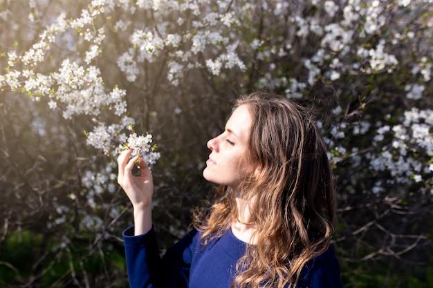 Jong meisje in een bloemrijke tuin bloemen snuiven