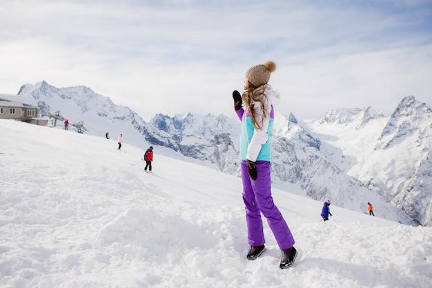 Jong meisje in een de winterkostuum dat in de bergen glimlacht