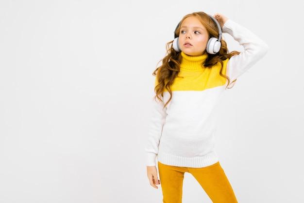 Jong meisje in een gele en witte trui luistert naar muziek en kijkt in de verte
