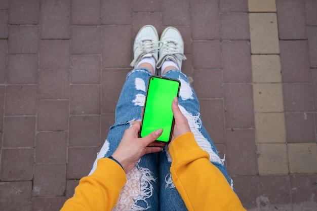 Jong meisje in een gele trui houdt een telefoon met een groen scherm op haar knieën