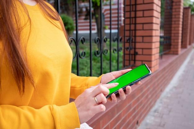 Jong meisje in een gele trui houdt een telefoon met een groen scherm