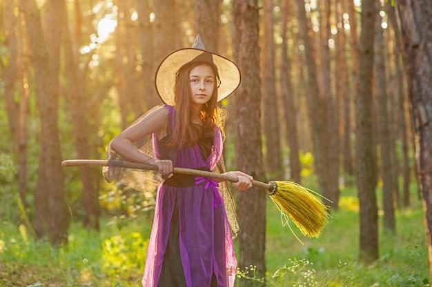 Jong meisje in een halloween-kostuum in het bos met een bezem. halloween.