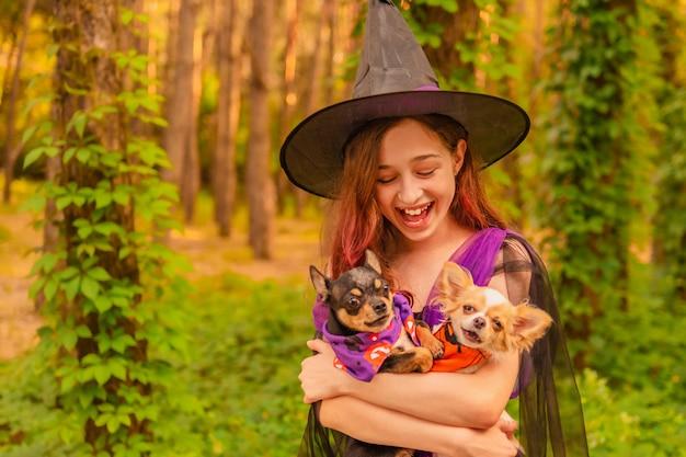 Jong meisje in een halloween-kostuum met twee chihuahuahonden in het bos. halloween-concept.