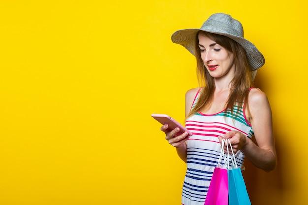 Jong meisje in een hoed en een gestreepte jurk lachend kijken naar de telefoon en boodschappentassen te houden