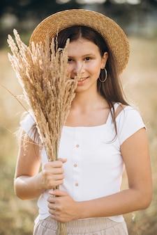 Jong meisje in een hoed op een gebied van tarwe