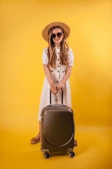 Jong meisje in een hoed staat met een koffer op een gele achtergrond