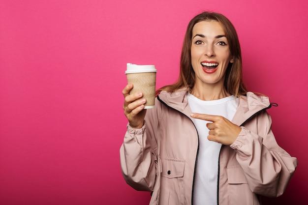 Jong meisje in een jas houdt een vel papier vast en wijst ernaar met een vinger op een roze oppervlak