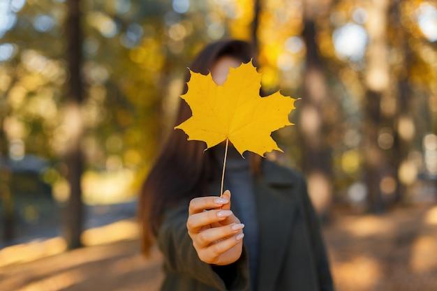 Jong meisje in een jas houdt in haar handen een geel herfstblad in het park op een warme herfstdag. gouden esdoornblad in vrouwelijke handen