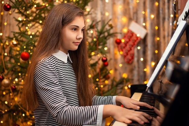 Jong meisje in een jurk met lang haar zitten in de buurt van de piano en spelen, kerstboom op de achtergrond. concept van het nieuwe jaar, gezinsvakanties.