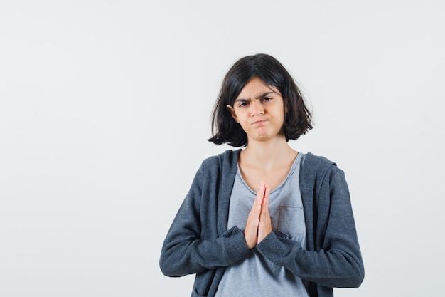 Jong meisje in een lichtgrijs t-shirt en een donkergrijze hoodie met rits aan de voorkant die namaste-gebaar toont en er serieus uitziet