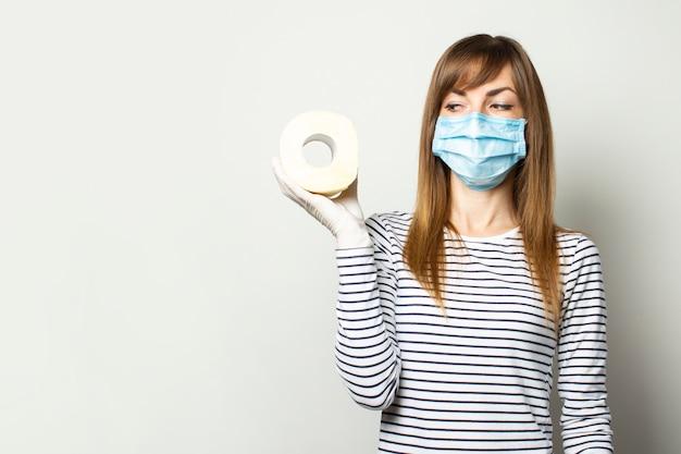 Jong meisje in een medisch masker en medische handschoenen met een rol wc-papier en kijken naar het op een lichte muur. concept quarantaine, tekort, paniek